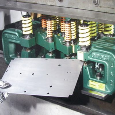 One Hit Many Holes - Here a dedicated setup on a keyed mounting template produces multiple operations including corner notching, round and shaped hole punching and lance & form. UniPunch engineers can help layout the tooling for your part.